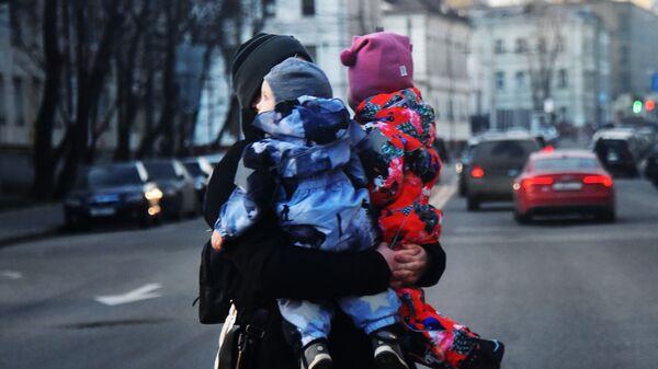 Женщина с двумя детьми на руках переходит дорогу. Архивное фото