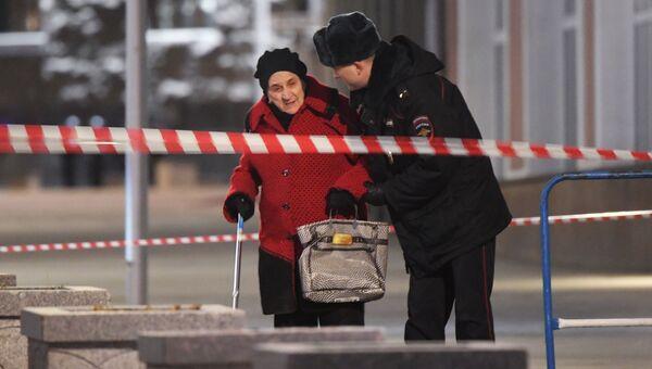 Сотрудник полиции помогает женщине пройти в зоне оцепления недалеко от здания ФСБ на Лубянской площади в Москве, где произошла стрельба