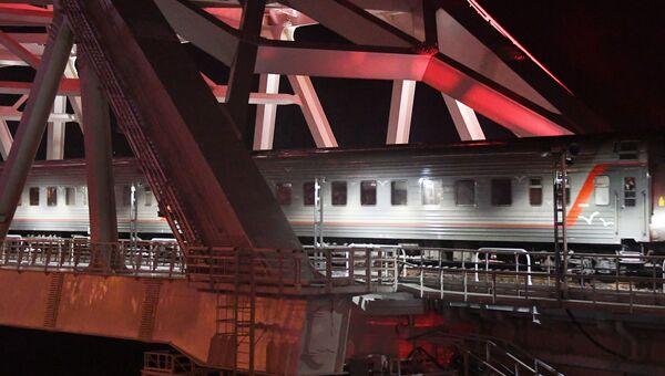 Пассажирский поезд Таврия идет под аркой Крымского моста