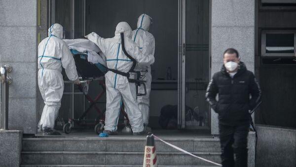 Медперсонал доставляет зараженного коронавирусом пациента в одну из больниц города Ухань в Китае