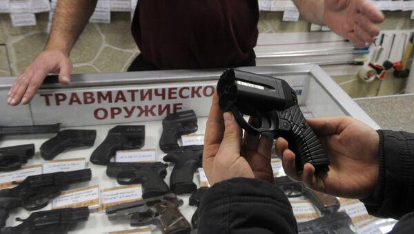 Покупатель осматривает травматический пистолет Оса в одном из оружейных магазинов Москвы