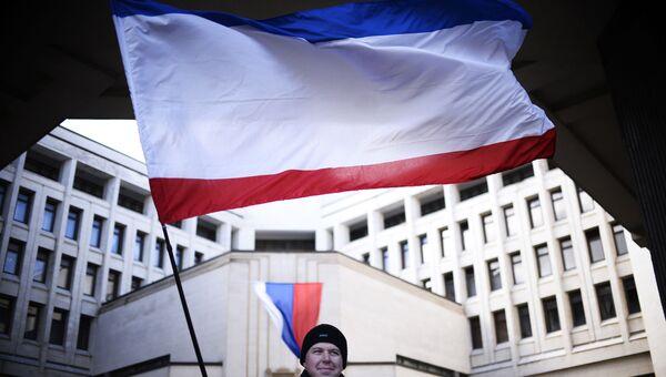 Мужчина с флагом Крыма у здания Госсовета РК