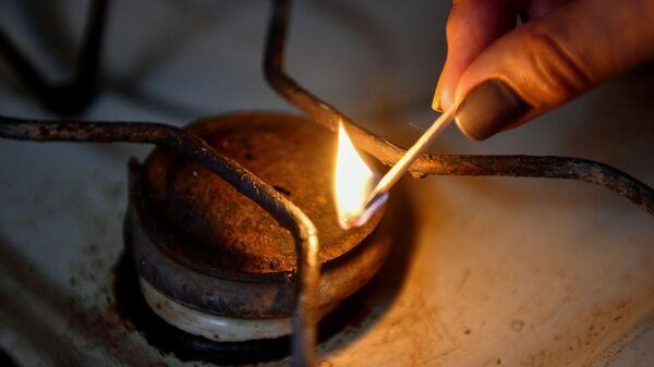 Женщина зажигает конфорку газовой плиты в жилом доме города Симферополь
