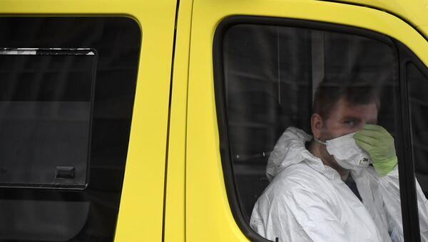 Медицинский работник в защитном костюме в реанимобиле