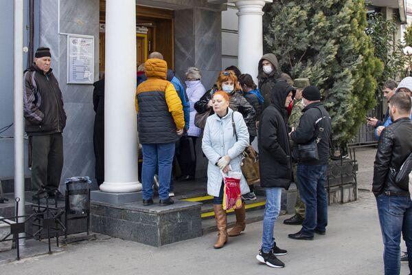 В помещение банка Россия пускают по-одному. Но народ стоит в очереди снаружи.  Очень тесной очереди.