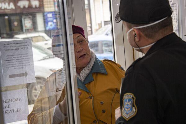 Охранник в маске объясняет пожилой посетительнице без маски, что по крайней мере неделю сюда приходить смысла нет.