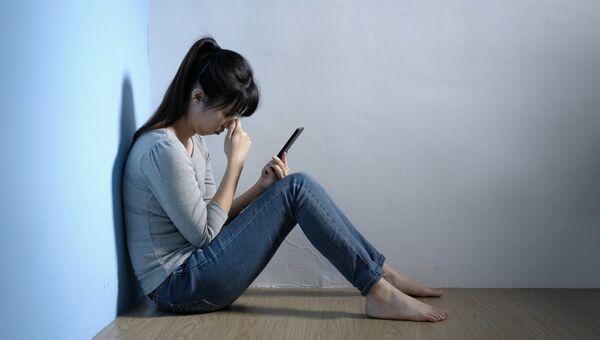 Грустная девушка с мобильным телефоном