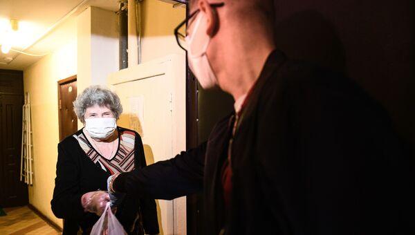 Волонтер штаба Мосволонтер передает женщине пакет с продуктовым заказом