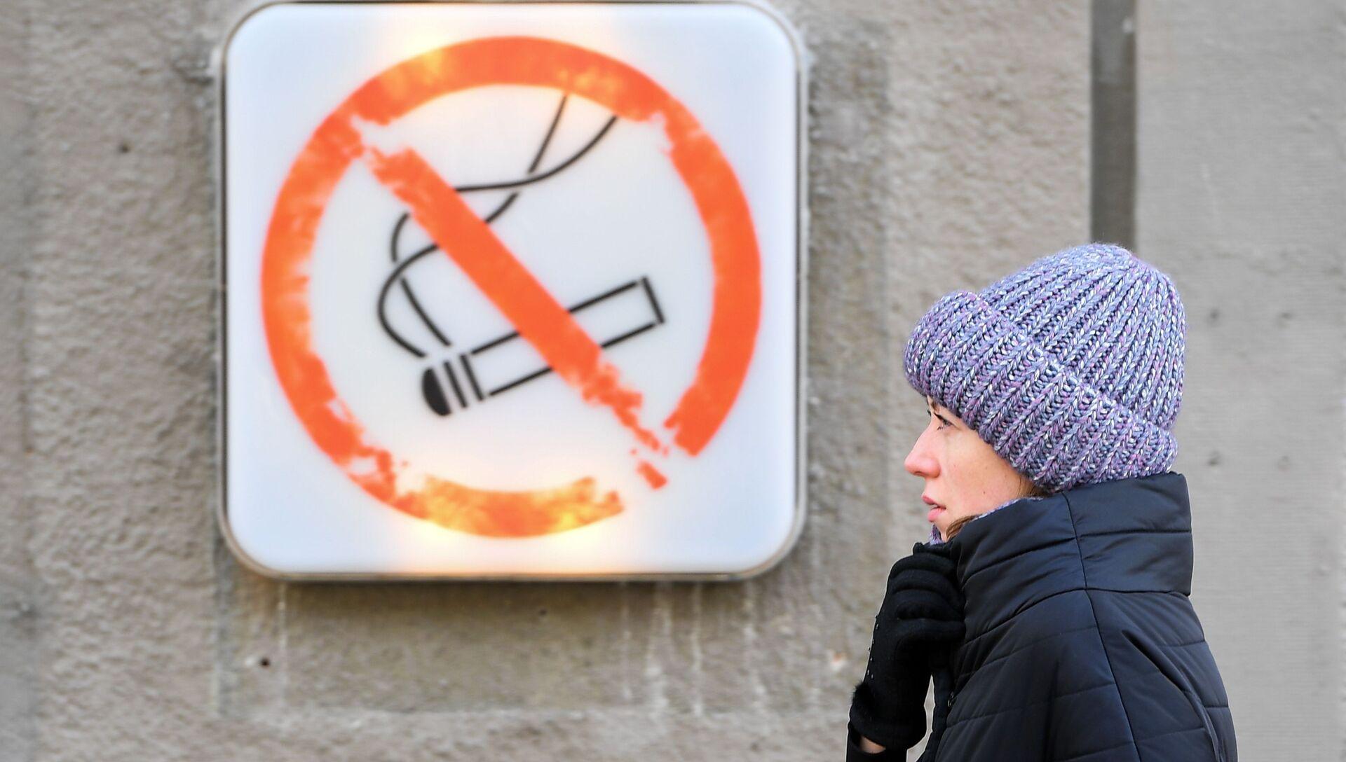 Женщина около таблички курение запрещено в Москве - РИА Новости, 1920, 13.11.2020