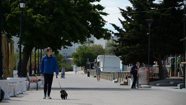 Мальчик гуляет с собакой на набережной в Севастополе. Пляж Омега