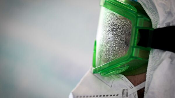 Врач в запотевших защитных очках во время работы в госпитале для лечения зараженных коронавирусной инфекцией COVID-19