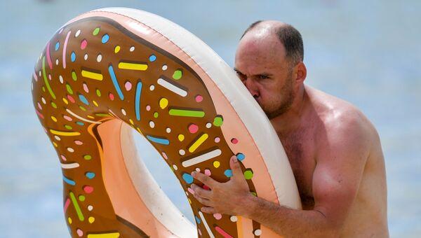 Мужчина надувает круг на пляже в Евпатории